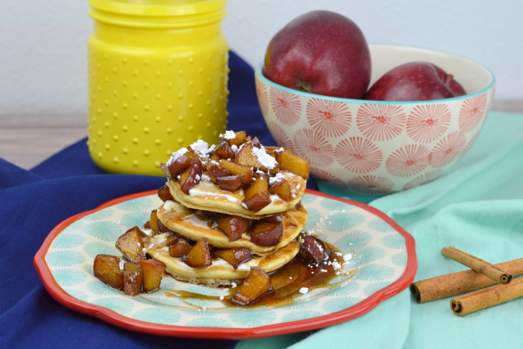 Old fashioned and fluffy pancakes topped with sour cream, fresh apples cooked in a cinnamon syrup glaze and powdered sugar make these Apple Cinnamon Pancakes the best fall recipe for breakfast, brunch, or dinner.